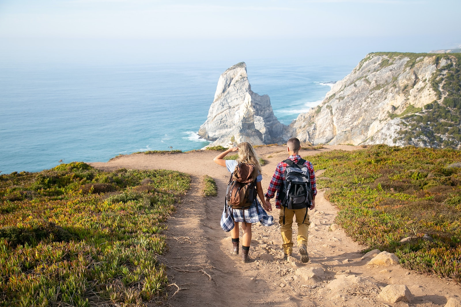 Couple hiking on cliff looking at ocean
